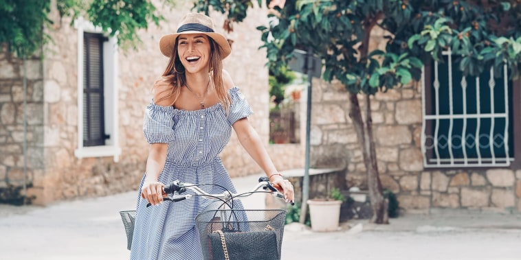 Woman with a bicycle, wearing a hat and blue dress