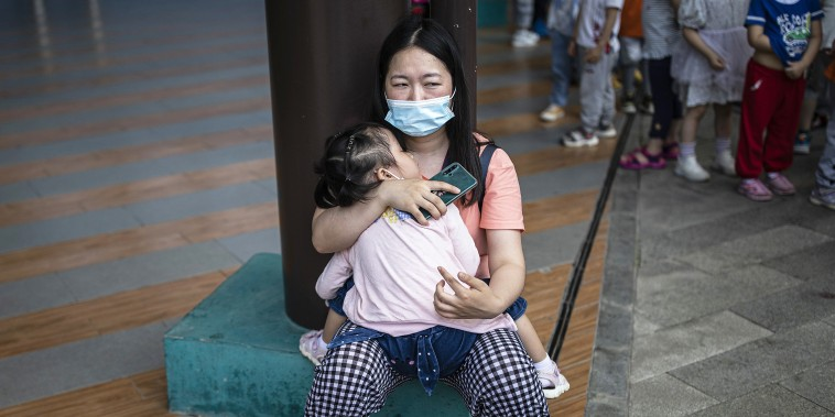 A woman carries her sleeping child at a community square