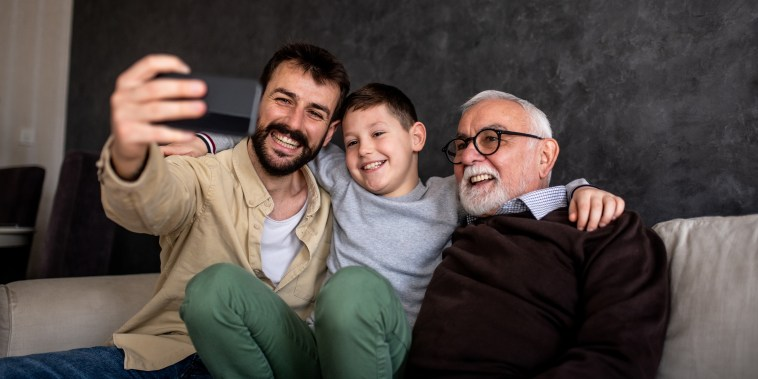 A young adult man is holding his mobile phone and taking a selfie with his family. It is Father's day and grandson, father, and grandfather are enjoying their time together.