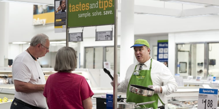 In this June 5, 2014 file photo, Rick Patanella, right, offers bacon samples to Karla and Gary Owens at Sam's Club in Bentonville, Ark.