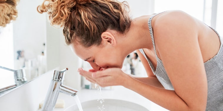 Woman washing her face at the bathroom sink in the morning