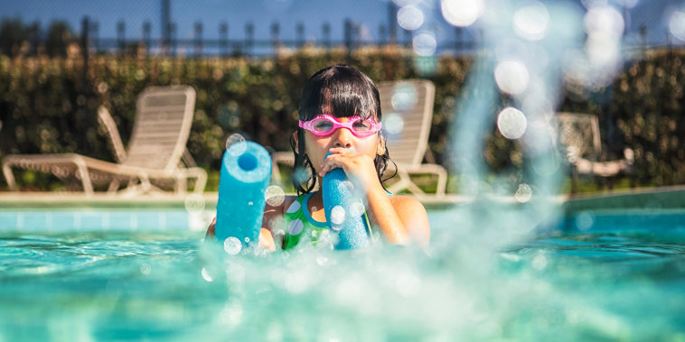 Little girl wearing goggles squirting water with a pool noodle