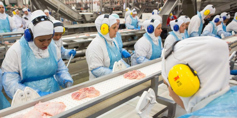 Image: People work at a production line of the JBS-Friboi chicken processing plant in Lapa, Parana State, Brazil.