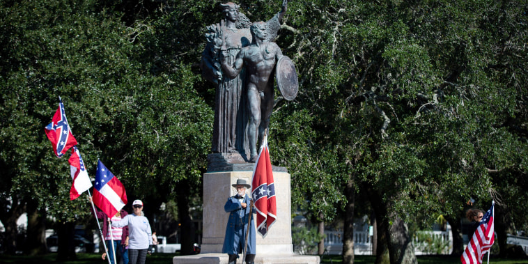 """Braxton Spivey holds a confederate battle flag dressed in a Confederate army uniform during a pro-Confederate flag protest by a group called \""""Flags of the South\"""" in front of The Confederate Defenders of Charleston statue at The Battery in historic downtow"""