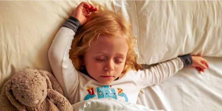 Young girl sleeping with stuffed rabbit