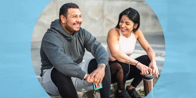 Man and Woman sitting on the pavement wearing workout gear