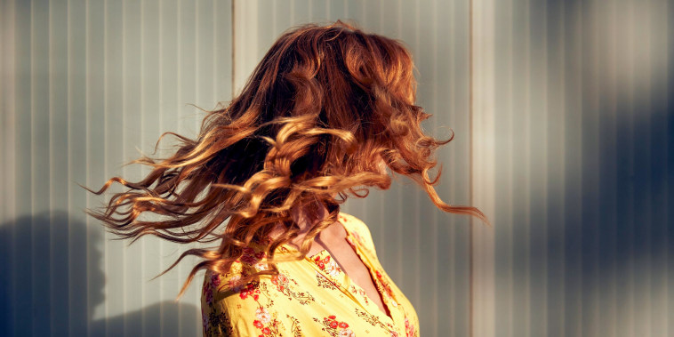 Red-haired woman shaking her hair