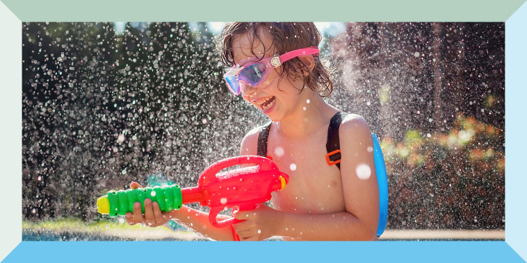 Little boy playing with a water gun outside