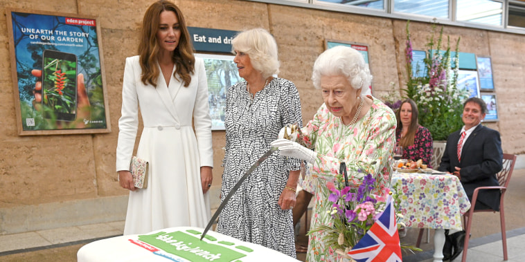 Queen Elizabeth II attempts to cut a cake with a sword