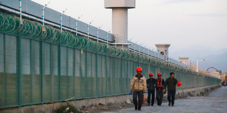 Image: Workers walk by the perimeter fence of what is officially known as a vocational skills education centre in Dabancheng in Xinjiang Uighur Autonomous Region, China.