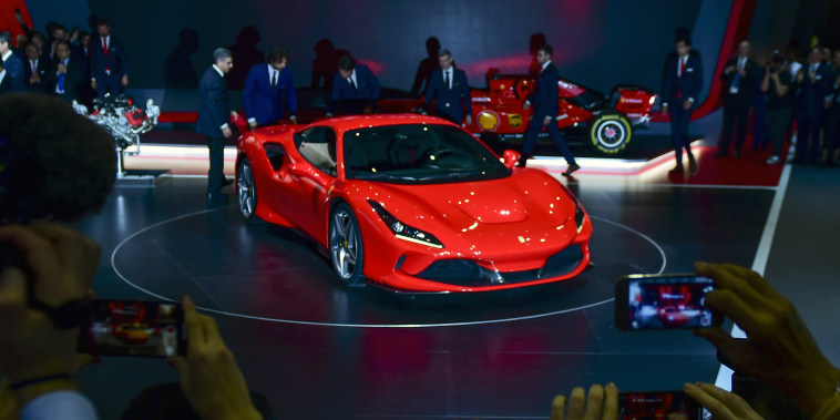 Image: Attendees take pictures of the Ferrari NV F8 Tributo on the opening day of the Geneva International Motor Show on March 5, 2019.