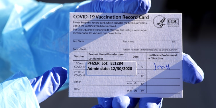 Dr. Kishore Nath holds a vaccination card provided to residents who have been given the Pfizer Covid-19 vaccine at Viamonte, a retirement community in Walnut Creek, Calif., on Dec. 30, 2020.