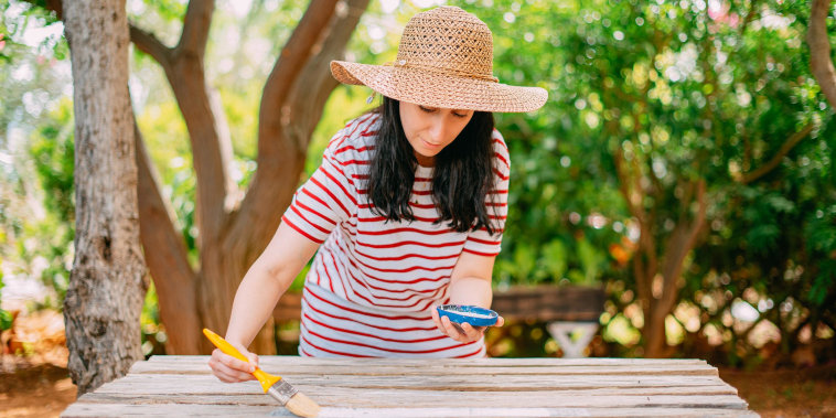 Woman Painting Wooden Table. DIY in the Garden