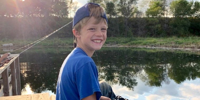 A smiling young boy in a blue shirt and backwards baseball cap holds a fishing rod over water