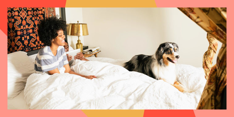 Woman sitting with dog in bed