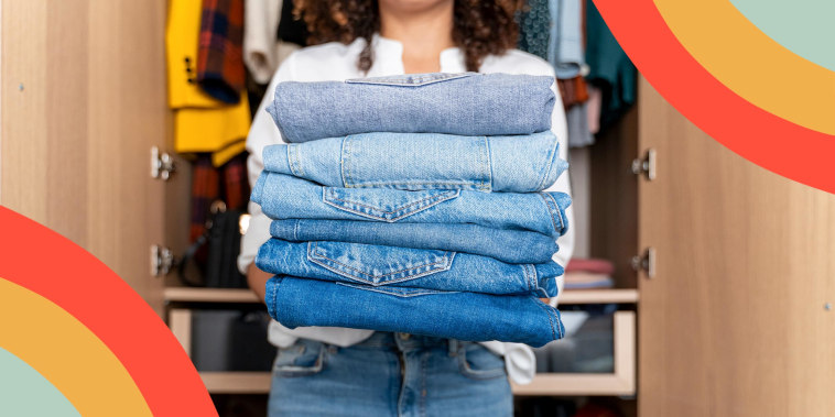 Woman standing on front of wardrobe holding stack of blue jeans