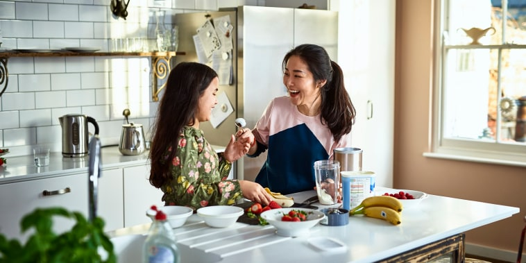 Mother teasing daughter in kitchen whilst making smoothies