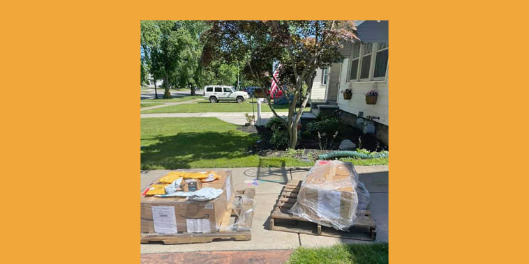 piles of boxes sit on the driveway of a suburban neighborhood