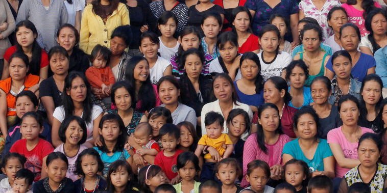 Image: Ziona's family members pose for group photograph outside their residence in Baktawng village in the northeastern Indian state of Mizoram,