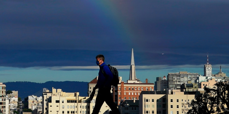 A man wearing a face mask crosses the street under a rainbow in San Francisco, on Feb. 1, 2021.