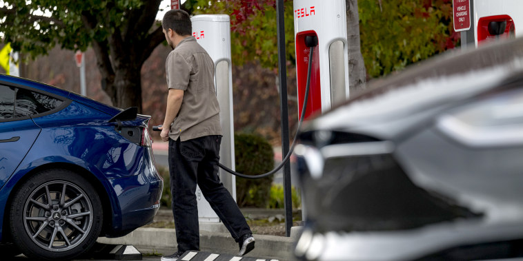 A person prepares to charge a Tesla Inc. vehicle at a charging station in Richmond, Calif., on Nov. 17, 2020.