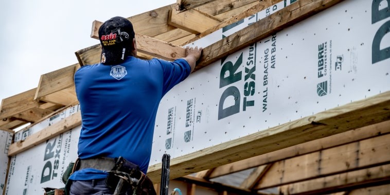 A worker installs wood on the exterior frame of a home under construction in the CastleRock Communities Sunfield residential development in Buda, Texas, on May 15, 2021.