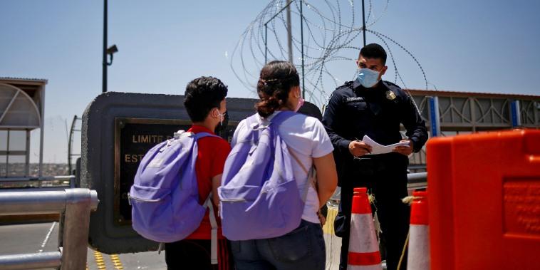 Image: Migrants from Central America walk across the Paso del Norte international border bridge in Ciudad Juarez