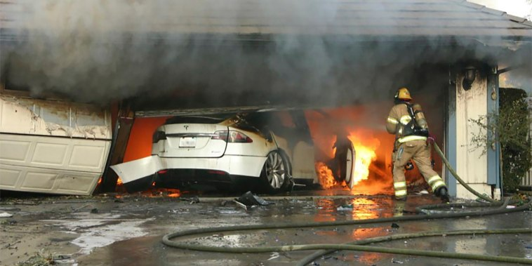 The Orange County Fire Authority battles a fire from a burning Tesla inside a garage in Orange County, Calif., in 2017.  When firefighters removed the SUV from the garage to assess the fire, they identified the fuel source as the SUV's high-voltage battery pack.
