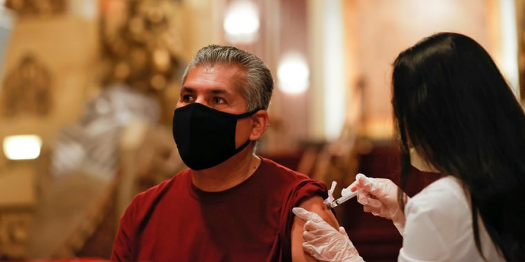 """Image: Jesus Oronoz receives a shot of the Johnson & Johnson coronavirus disease (COVID-19) vaccine with a chance to win a pair of tickets to see \""""Hamilton\"""" at a pop-up vaccination clinic at Pantages theatre in Los Angeles"""