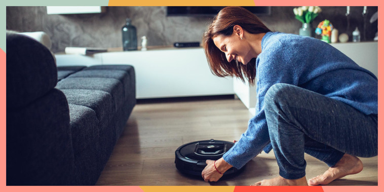 Woman holding a robot vacuum in her living room