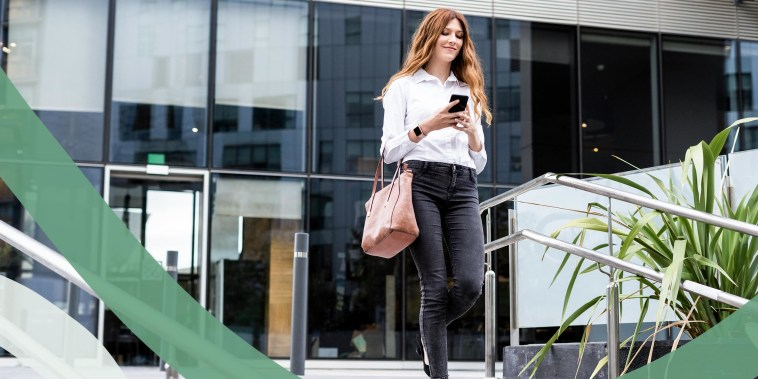 Young businesswoman walking down stairs, using smartphone