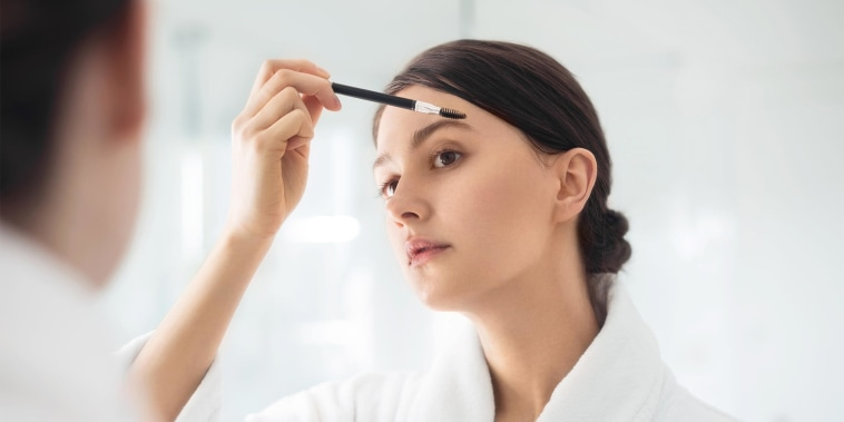 A young woman brushing the eyebrows while looking in the mirror