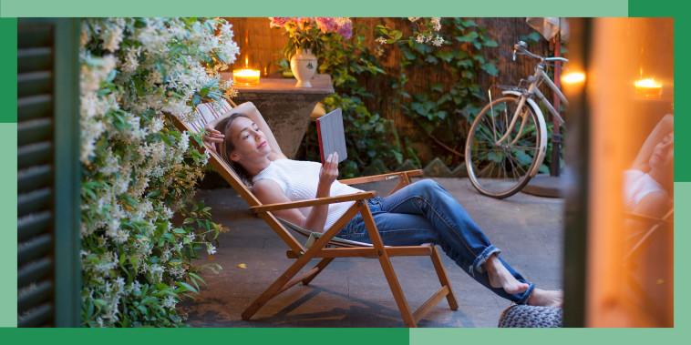 Woman relaxing on deck chair in backyard at dusk, reading on digital tablet