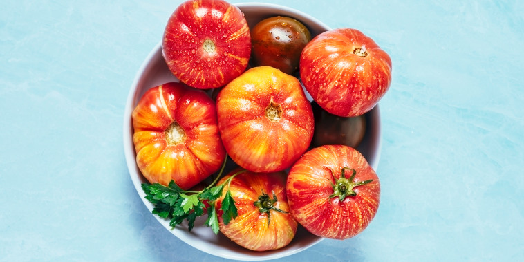 Bowl of heirloom tomatoes on blue background