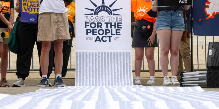Image: A petition with thousands of signatures is unveiled during a rally outside the U.S. Supreme Court in Washington in support of the For the People Act