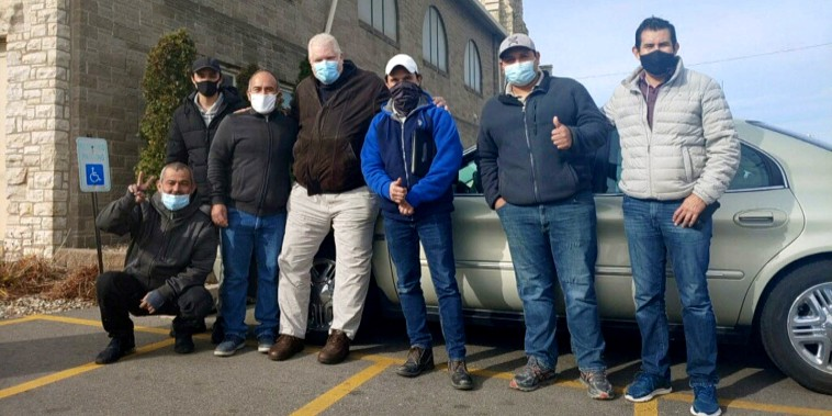 The six construction workers from Texas who stopped receiving pay for their work in Cedar Rapids, Iowa flank John Greve, pastor of Grace Episcopal Church, who fed and housed them after the learning of their situation.