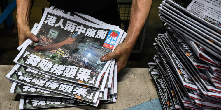 Image: An Apple Daily employee works in the printing room after the last edition of the newspaper is printed in Hong Kong,