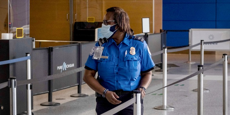Image: A Transportation Safety Administration agent (TSA) stands near a security checkpoint in Detroit