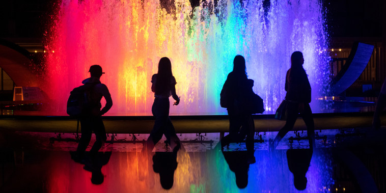 People walk past the fountain at Lincoln Center for the Performing Arts lit up in Pride colors on June 2, 2021, in New York.
