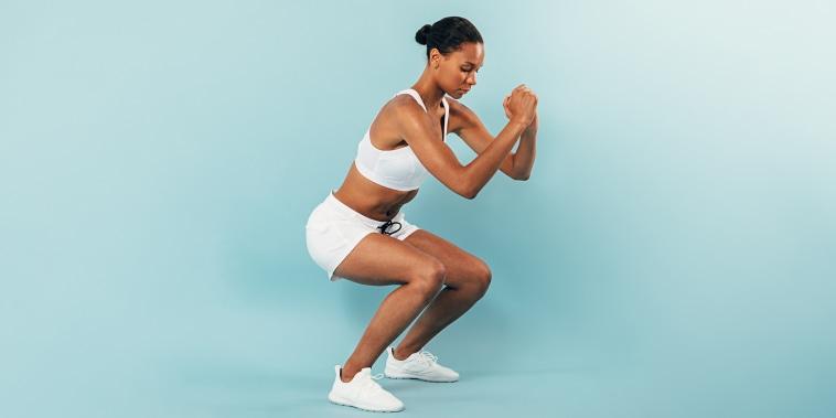 Full Length Of Woman Exercising Against Blue Background