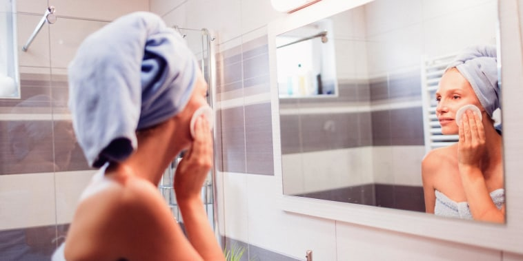 Woman cleaning her skin in bathroom