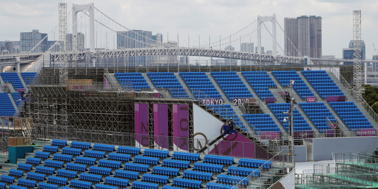 Construction workers are seen around spectators' seats in preparation for the Tokyo 2020 Olympic Games