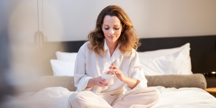 Woman sitting in her bed putting on lotion