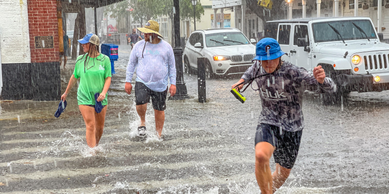 Pedestrians dash across the intersection of Greene and Duval streets as heavy winds and rain associated with Tropical Storm Elsa passes Key West, Fla., on July 6, 2021.