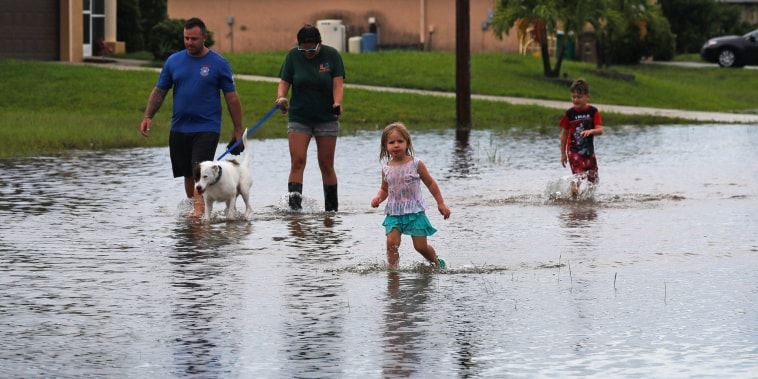 Image: Residents wade through their flooded street in Cape Coral, Fla., on July 7, 2021.
