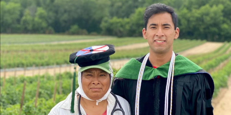 Young man in graduation gown next to woman in a field