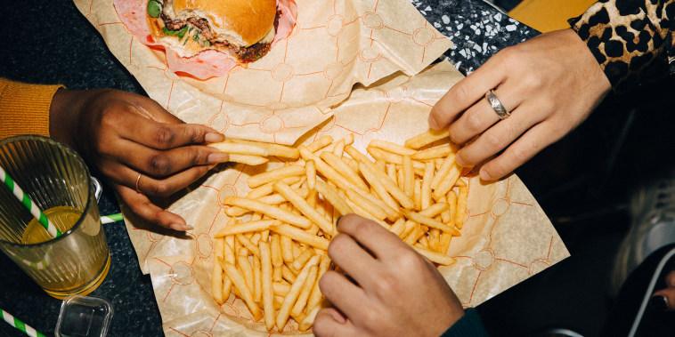 High angle view of friends eating burger and french fries at table in cafe