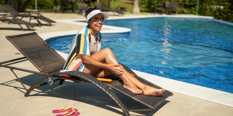 Smiling tourist relaxing beside the pool putting on lotion