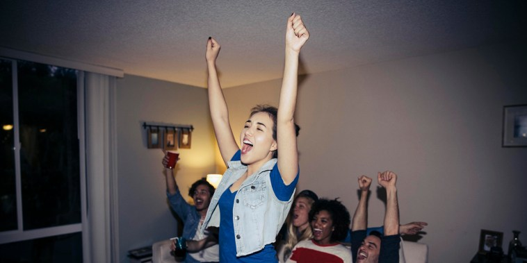 Friends cheering while watching sports on TV at home