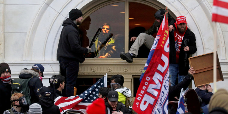 A mob of supporters of then-President Donald Trump climb through a window they broke as they storm the Capitol on Jan. 6, 2021.